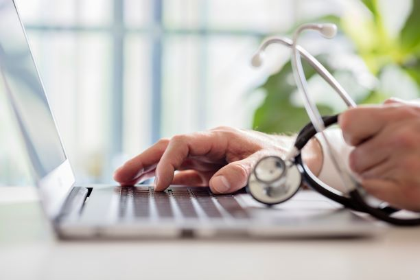 Medical professional typing on laptop.